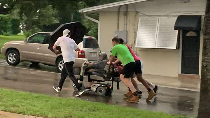 Young Men Push Elderly Woman In Broken Scooter Home In The Pouring Rain